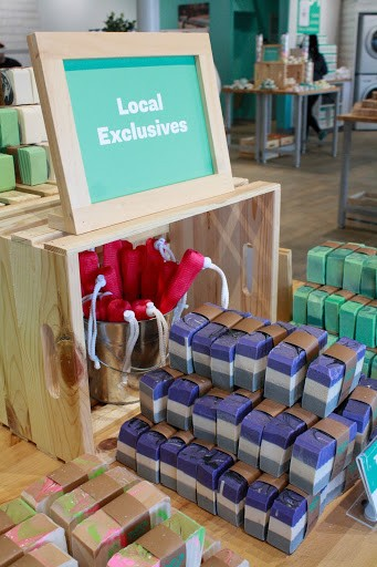"A placard reading ""Local Exclusives"" sits amid homemade soaps."