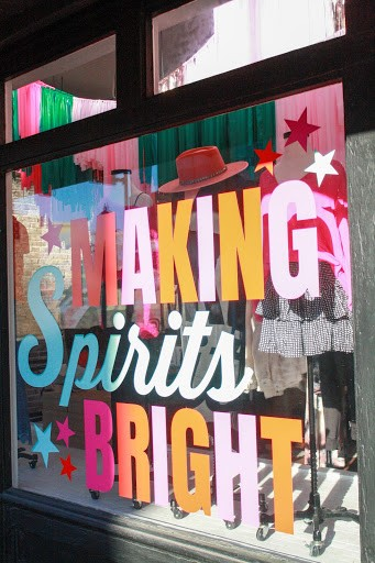 "A colorful holiday window display reads ""Making Spirits Bright""."