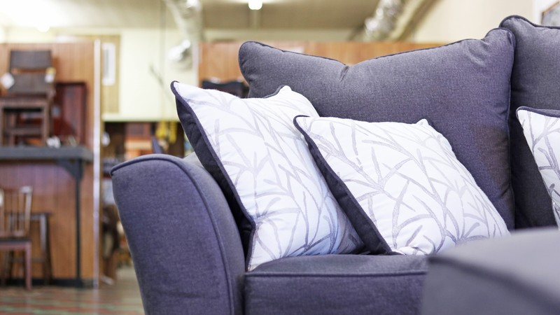 A grey couch and white throw pillows in a furniture store.