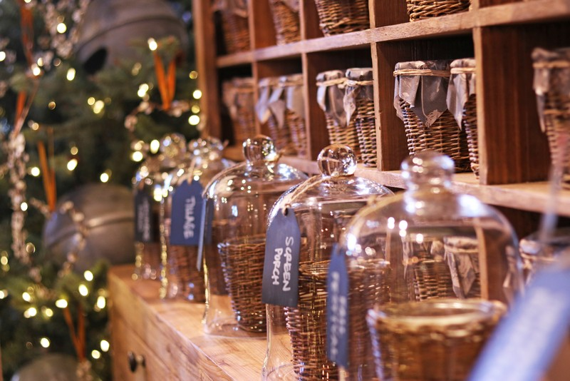 Numerous fall-scented candles in woven baskets in front of a lighted Christmas Tree.