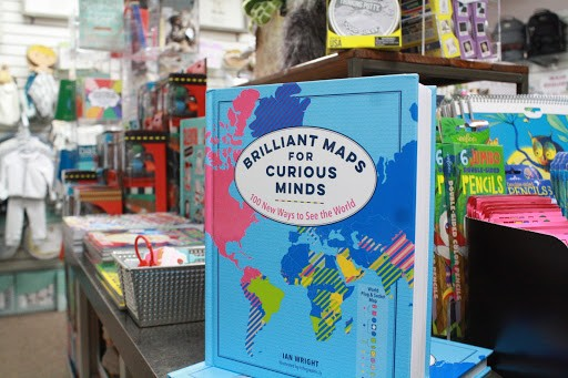 "A book on a shelf reads ""Brilliant Maps for Curious Minds""."