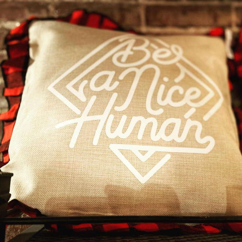 "A burlap throw pillow with the caption ""Be A Nice Human""."