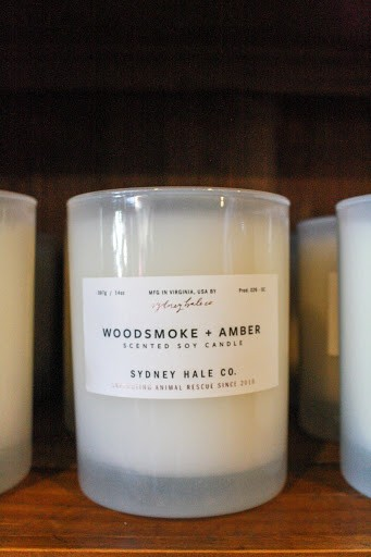 "A glass-enclosed candle reads ""Woodsmoke and Amber""."